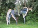 Steel and concrete sculpture of horse with figure. view obscured by overhanging branch